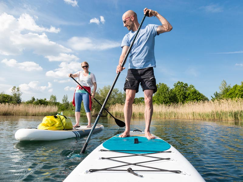 A man and a woman stand up paddle boarding on a lake