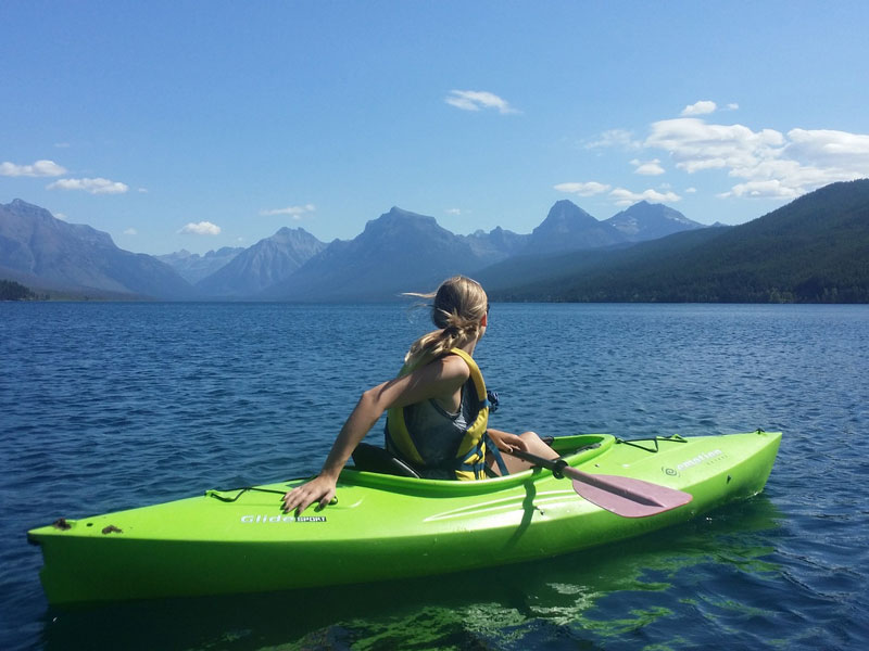 A woman sitting in a kayak on a lake looking at mountains