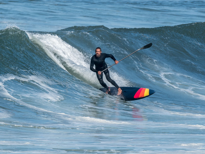 A man surfing on a stand up paddle boar wearing a wetsuit.