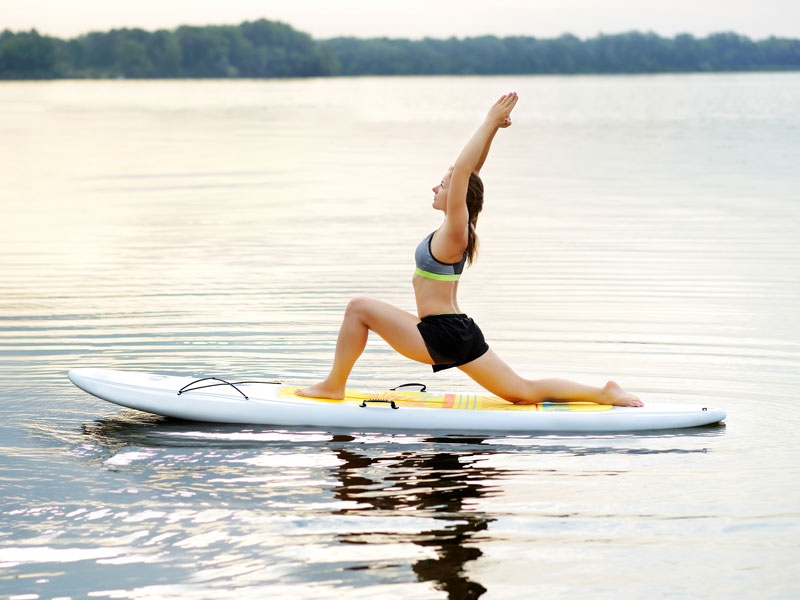 woman practising yoga on a stand up paddleboard on a lake