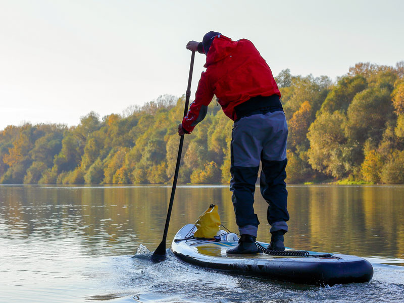 A man paddling down a river on a stand up paddle board