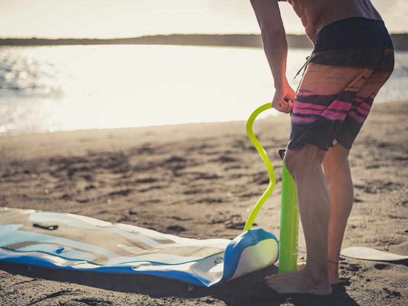 A man inflating an inflatable paddle board on the beach.
