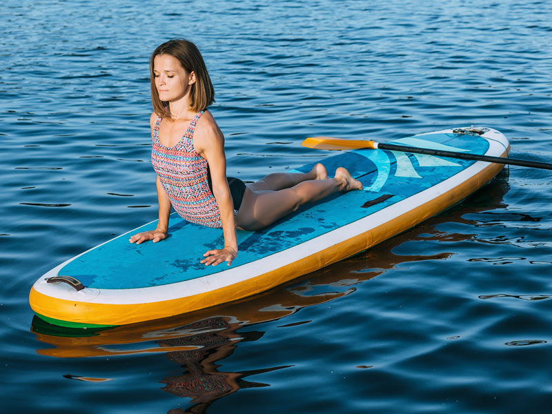 A woman practicing yoga on a yoga paddle board.