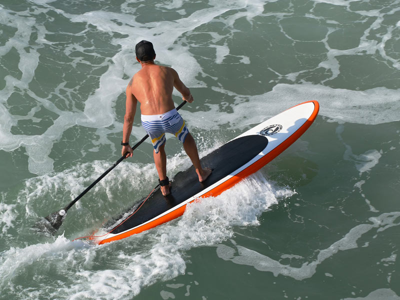 A man riding a SUP Surf paddle board. One of the types of paddle boards.