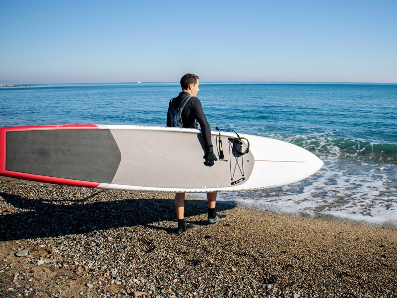 A man carrying one of the types of paddle boards into the sea, a touring paddle board.