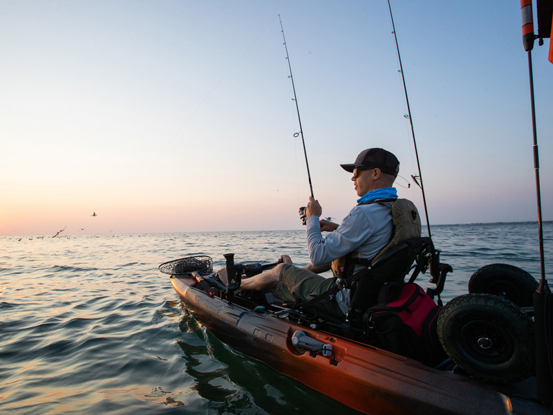 A man fishing from a specialist fishing sit on top kayak