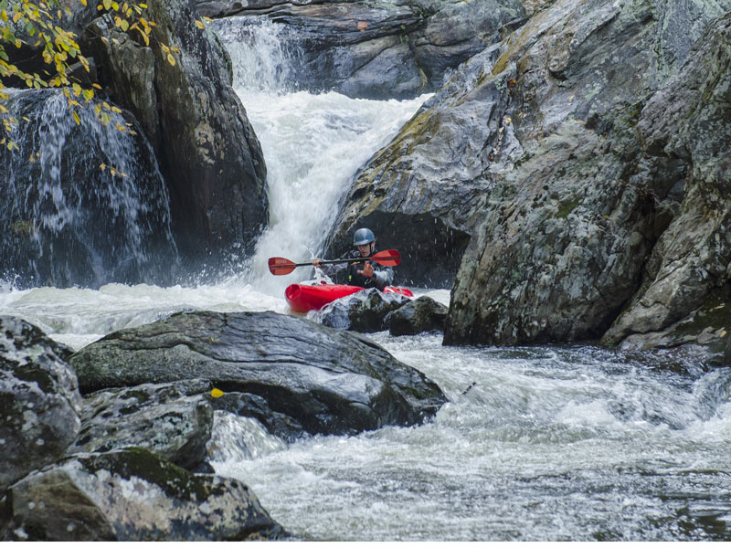 A man whitewater kayaking down a raging river with waterfalls