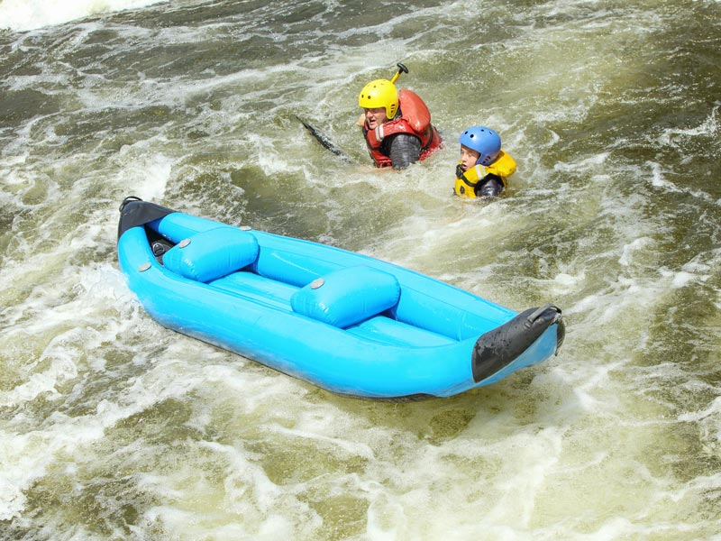 Two people falling out of a canoe in white water